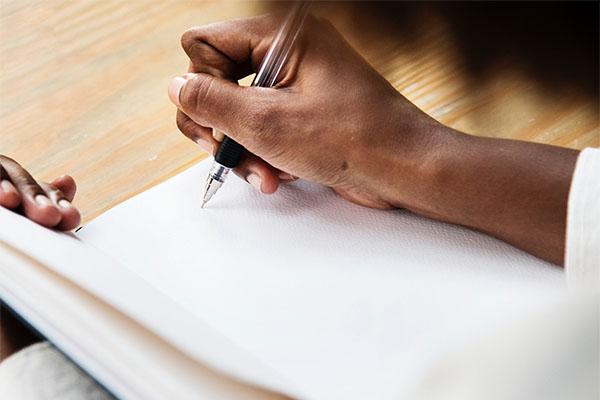 person uses pen on book, photo credit rawpixel.com